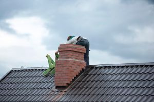 Worker on the roof repairs brick chimney