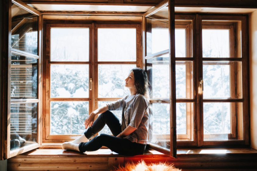 Woman sitting on brown wooden window frame