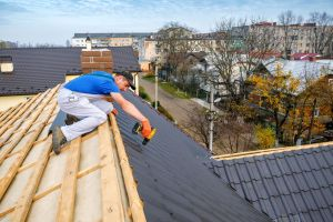 a professional master (roofer) with electric screwdriver covers repairs the roof
