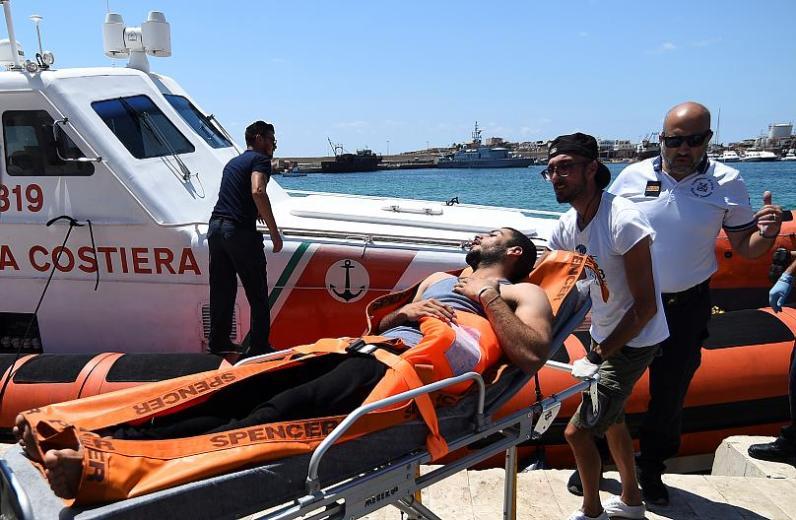 Un migrante que saltó del barco de rescate español Open Arms es llevado en una camilla, en Lampedusa REUTERS / Guglielmo Mangiapane