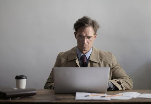 concentrated-man-in-eyewear-working-on-laptop-in-light-3931546