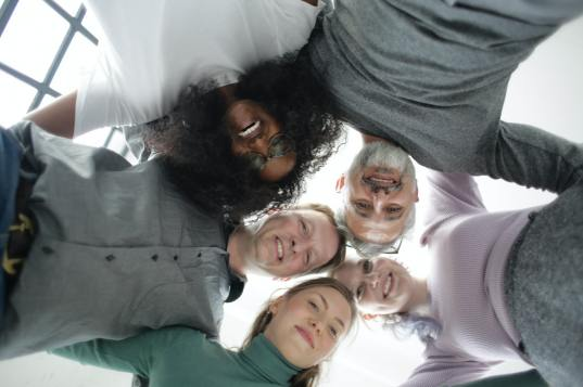 from-below-of-cheerful-multiethnic-coworkers-embracing-each-3931556