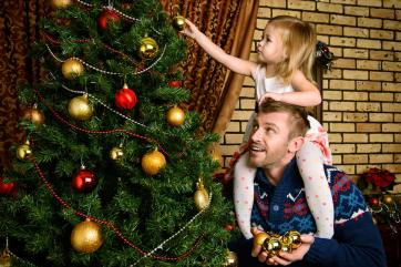 picture of a father and daughter decorating a Christmas tree (or xmas tree)