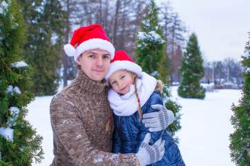 picture of a father and daughter at a Christmas tree (or xmas tree) farm