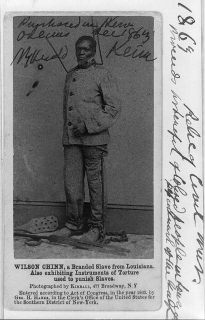 Wilson Chinn, a branded slave from Louisiana, exhibiting instruments of torture used to punish slaves.