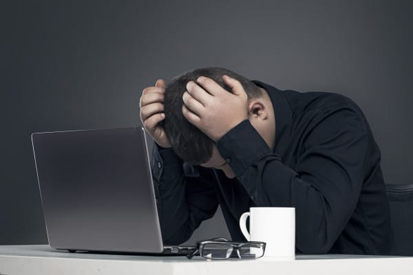 Man with his head in his hands over a laptop