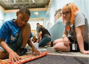 A young black boy and an orange haired white woman sit on the floor working on a yarn loom.