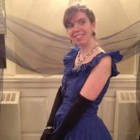 Picture of author Alli Hartley in a blue dress with long black gloves and fancy jewelry, standing in front of a black tulle fabric.