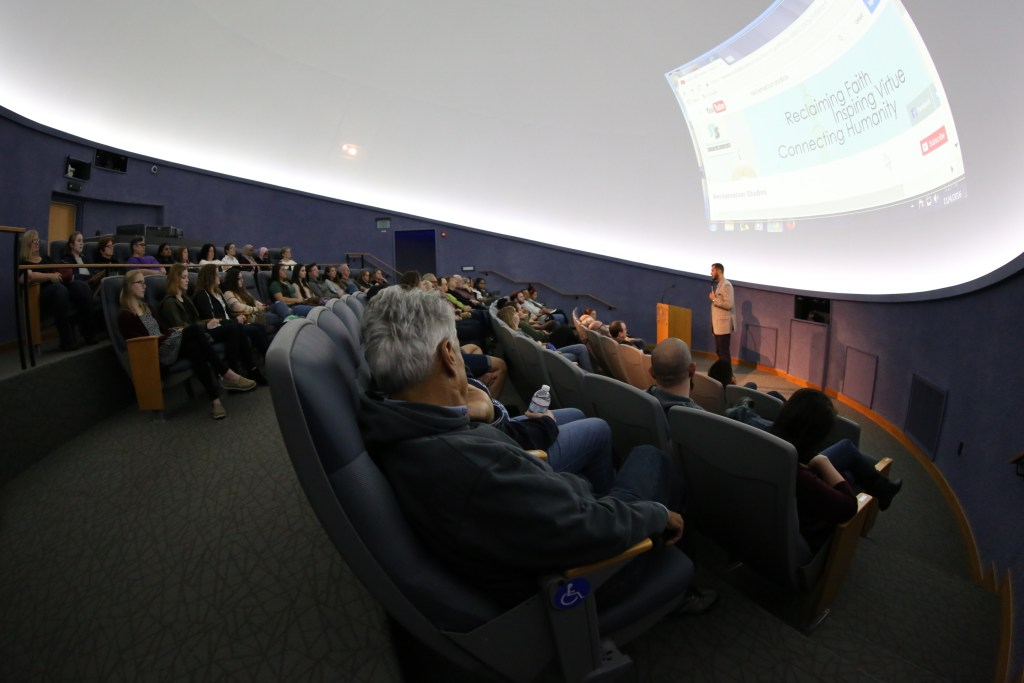Image of a large group watching a full screen presentation with a man speaking.