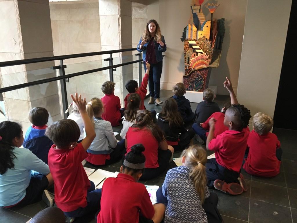 A teach stands discussing a sculpture with a group of students in front of her.