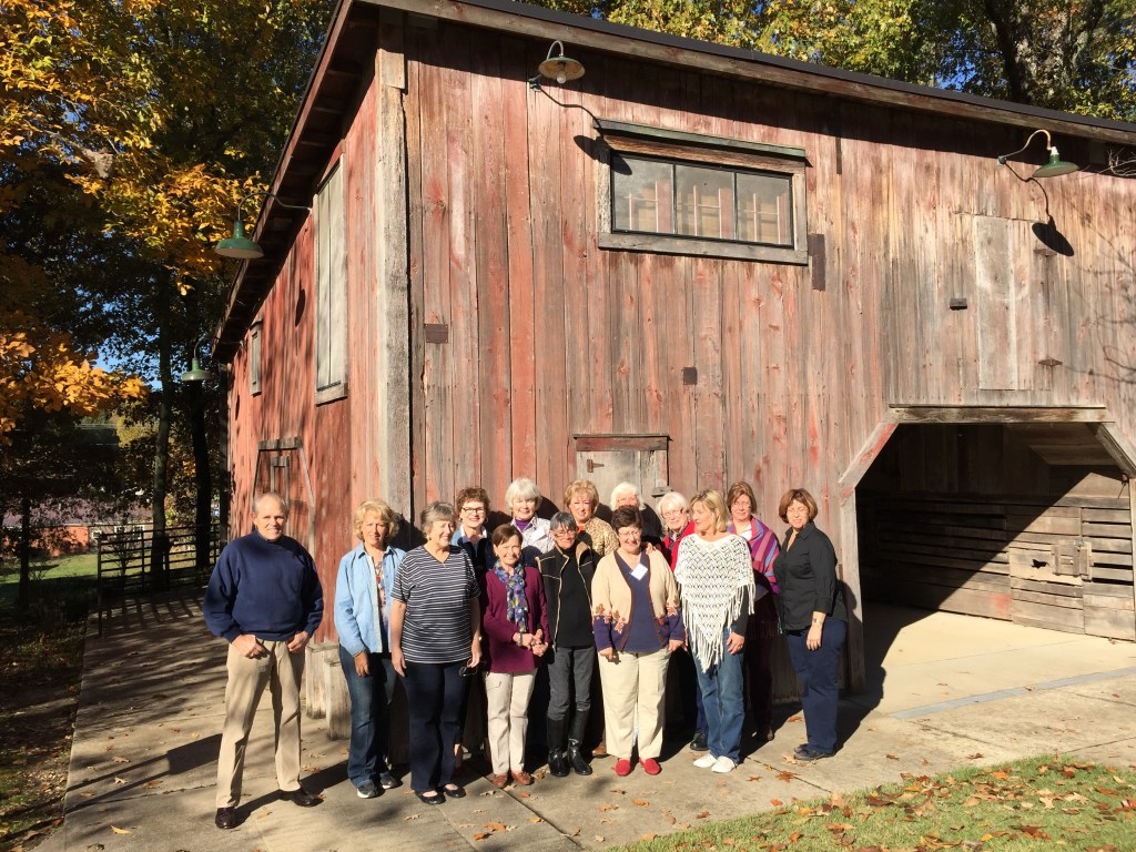 Group of 20 people standing in front of a rustic barn