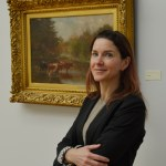 Woman stands smiling with her arms folded in front of her standing in front of a painting in a gilded frame she has long brown hair and is wearing a black blazer and grey shirt
