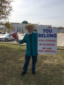 "Photo Of 53-Year-Old Justin Normand Outside The Islamic Center Of Irving Near Dallas, Texas Holding A Sign Stating ""You Belong. Stay Strong. Be Blessed. We Are One America."""