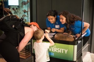 Two women help a young visitor learn about an object on exhibit