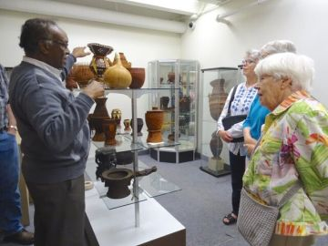 A man explains artifacts to ta group of three women in the museum