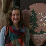Woman stands in front of a National Park Service sign wearing a multi-colored scarf.