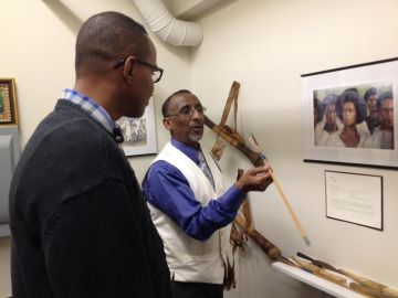 Two men examine an artifact in the museum