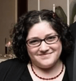 A woman smiles at the camera with short curly dark hair, wearing glasses a dark top and a red necklace.