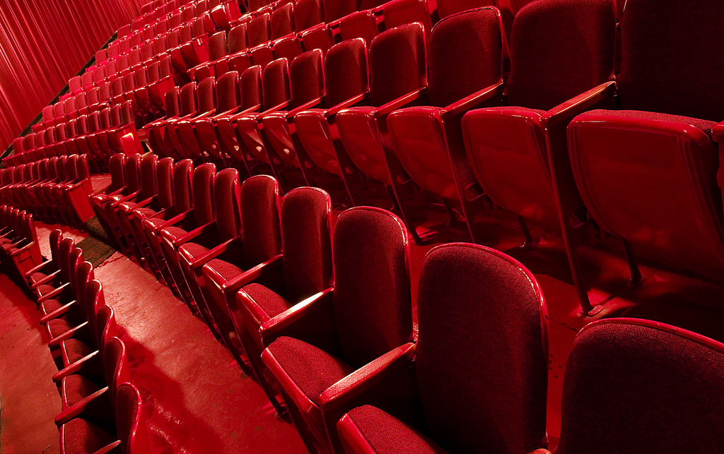 Red theatre seats in parallel rows fading into the distance