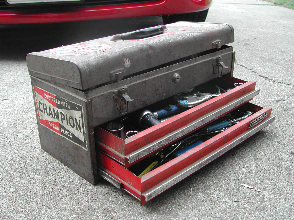"An old toolbox with a ""champion"" sticker on the side and two drawers partially open"