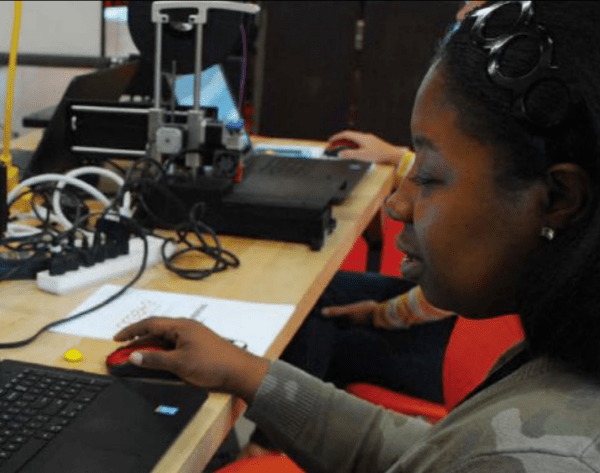 A young African-American woman types at a computer in a lab setting. Her face and torso are seen on the right of the image as she gazes at the computer screen (outside of the composition) on the left. Her hand is on the mouse and there is a there is another person, also on a black laptop, just visible behind her.