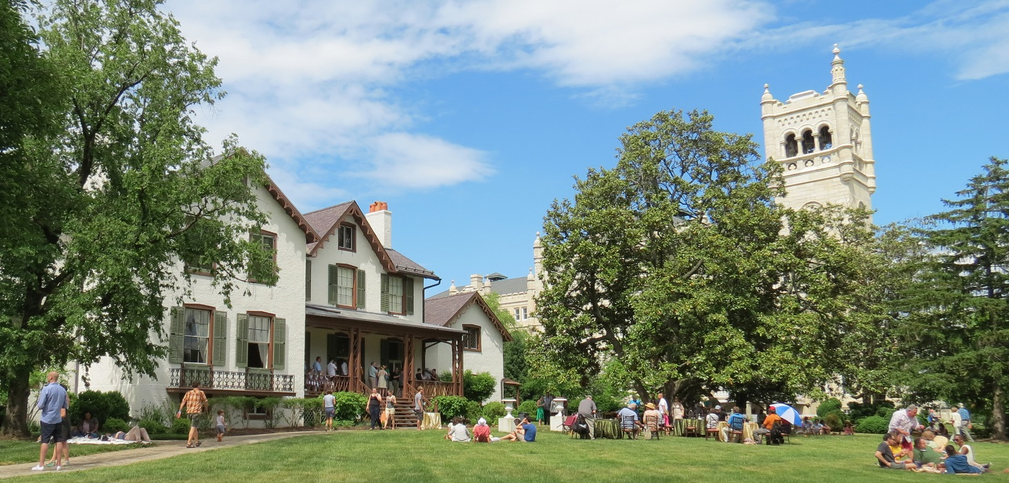 Image of the lawn and house with a group of people milling around.