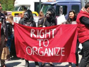 View of a group of people holding a sign that says Right to Organize. Two of the people are wearing gorilla masks.