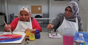 Two women sit facing the camera wearing head scarves and white aprons apparently painting artwork that is sitting on a grey table.