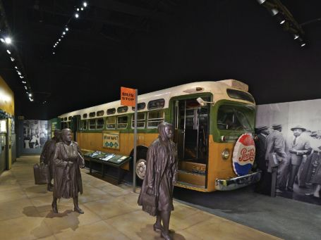 Image of a buss with grey statues in front inside an exhibition.