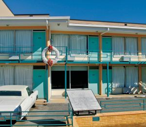Exterior shot of the Lorraine Motel with a large white wreath with red flowers at the top and bottom hung on the second floor railing.