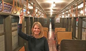 Meredith Gregory shown holding on to the handles in an empty subway car.