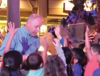 Phil Manning shown speaking in front of a group of young children with their hands raised.