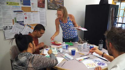 A woman stands at a table surrounded by three other people who are painting on white paper with paint palettes in front of them.