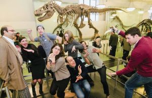 A group of Museum Hack staff standing on a platform in front of a Tyrannosaurus Rex skeleton.