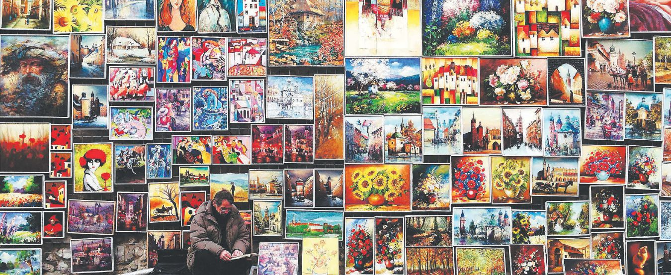 A man crouches in front of a large wall with a variety of oil paintings hanging on it.