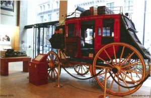 View of a red horse drawn carriage on display in a lobby.