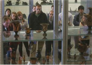 A group of people stand looking into a display case. The camera shot is taken through the display case from the other side.