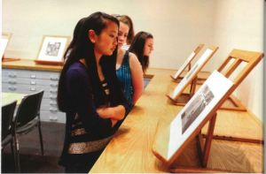 Several young women look at sketches displayed on top of map drawers on small easels.