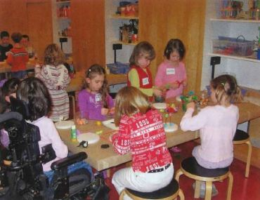 Children sitting around a table with a young girl in wheelchair at one end working on an art project.