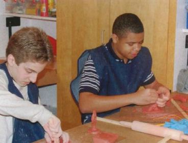 Two young men sit working side-by-side at a table working on an art project with clay.