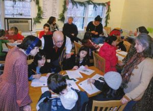 A group of young people sit around several wooden tables with adults overseeing a writing project.