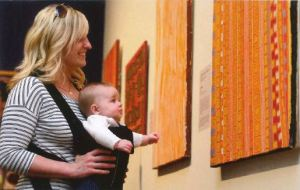 A blond woman holds a baby in a carrier looking at a colorful hung on the wall.