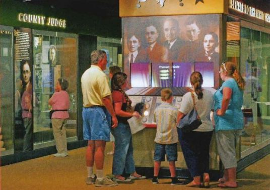 A group of people surround an exhibit panel.