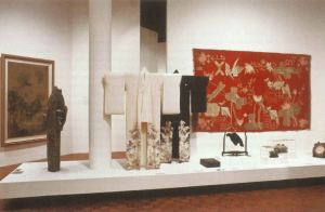 Two kimonos on stands with various other artifacts on a plinth in a gallery.