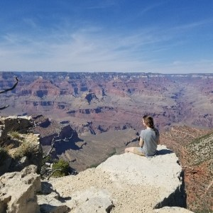 A woman sits on a rock ledge overlooking the Grand Canyon.