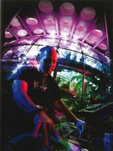 A man stands spinning records in a glass enclosed space. Taken with a fisheye lens.