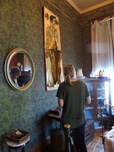 A woman looks toward a wall in a historic house with an anatomical drawing displayed.