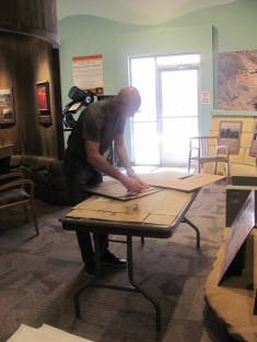 A bald man stands over a folding table working with the back of a picture frame.
