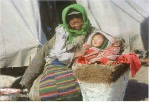 A mother holds her baby in a papoose next to her side.