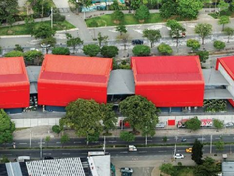 Four rectangular structures connected by gray passthroughs with red roofs sit in a stark landscape.